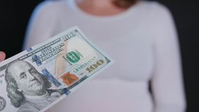 A Woman in White Sweater Receiving Cash. A women in a white sweater receiving cash US Dollars against a black background. Close-up shot Royalty Free Stock Images