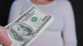 A Woman in White Sweater Receiving Cash. A women in a white sweater receiving cash US Dollars against a black background. Close-up shot Royalty Free Stock Photos