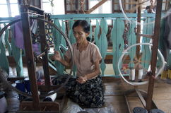 Women winding out silk to get it ready to weave. Burma stock photo
