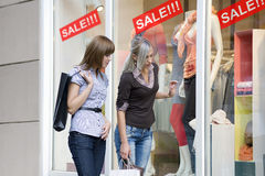 Women window shop. Two young women friends looking at a window shop during the sale Stock Photo