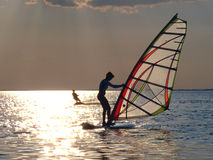 A women is windsurfing. A women is learning windsurfing at the sunset Stock Image