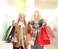 Women in winter clothes with shopping bags. Retail and sale concept - happy women in winter clothes with shopping bags Stock Image