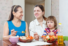 Women With Baby Girl Eats Vegetables Salad Royalty Free Stock Images