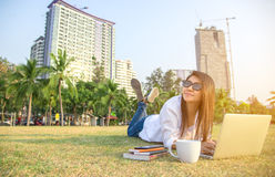 Women work in the park with the laptop and coffee,. Relax work, background city Royalty Free Stock Photos