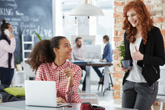 Women working in creative agency. Young women working in creative agency, talking and smiling stock images