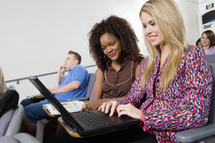Women Working On Laptop In Lecture Room. Beautiful young women working on laptop in lecture room Royalty Free Stock Photography