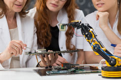 Women working on a mainboard. Cropped picture of three women working on a mainboard Royalty Free Stock Photography