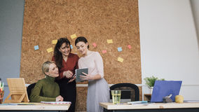Women Working In An Office. Women are working together in an office. One of the women is holding a digital tablet which they are all looking at Stock Photo