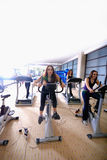 Women working out on spinning bikes at the gym royalty free stock images