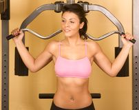 Women working out on weight-lifting machine. Attractive young female works out on weight-training machine Stock Images