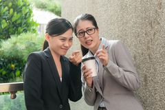Women workplace bullying conversation. Two Asian women enjoy workplace bullying conversation about another colleague rumor gossip and pointing outdoor of the stock photo