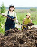 Women works with animal manure. Two women works with animal manure at field Royalty Free Stock Images