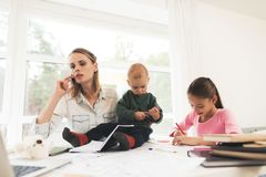 A woman works during maternity leave at home. A woman works and cares for a children at the same time. A women works during maternity leave at home. A women royalty free stock photos