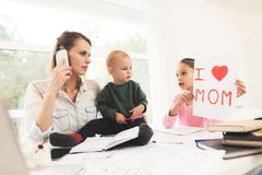 A woman works during maternity leave at home. A woman works and cares for a children at the same time. A women works during maternity leave at home. A women royalty free stock photo