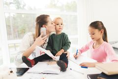 A woman works during maternity leave at home. A woman works and cares for a children at the same time. A women works during maternity leave at home. A women stock photo