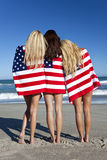 Women Wrapped in American Flags on a Beach. Three beautiful young women wearing bikinis and wrapped in American flags on a sunny beach stock image