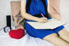 Women writing down on blank workbook or booklet while sitting on royalty free stock photos