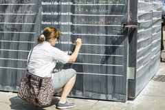 Women writing her wishes on the wall. Women is completing the sentence that starts with words: Before I die I want to ... . This horisontal image is from the ART Stock Photos