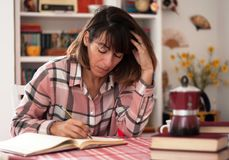 Women writing a new book. Young female book author sitting on her desk.  looking at her notes Stock Photo