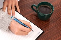 Women writing into the notebook on wooden desk and drink coffee royalty free stock images