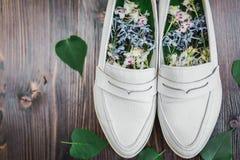 Women& x27 ; chaussures blanches de s avec les fleurs fraîches sur la semelle intérieure Image libre de droits