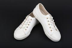 Women& x27 ; chaussures blanches de sport de s sur le fond foncé Photographie stock libre de droits