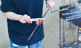 Women& x27;s hands cut barbecue meat Skewer on the grill Stock Photos