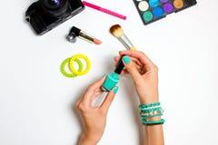 Women& x27; s manicured las manos en el color de la turquesa que llevaba a cabo esmalte de uñas Fotografía de archivo libre de regalías