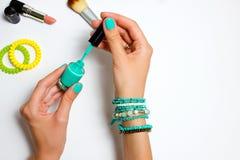 Women& x27; s manicured las manos en el color de la turquesa que llevaba a cabo esmalte de uñas Foto de archivo