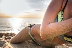 Women's sexy body on the yellow sand beach Stock Image