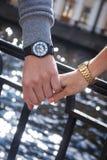 Women& x27; s x27 i men&; s zegarki man& x27; s ręka trzyma kobiety Zdjęcie Stock