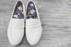 Women& x27; zapatos blancos y flores de s dentro Imagenes de archivo