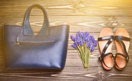 Women& X27;s Accessories On The Wooden Floor. Sandals, Women& X27;s Bag, A Bouquet Of Dove Flowers. Top View. Flat Lay. Royalty Free Stock Image