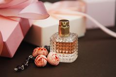Free Women& X27;s Pink Perfume In Beautiful Bottle And Artificialt Flowers Bracelet On Brown Background With Gift Boxes On Background. Stock Photography - 111031142