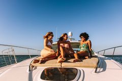 Women on the yacht deck sailing the sea. Group of young women sitting on the yacht deck sailing the sea. Three female friends in swimsuits relaxing and talking Stock Photos