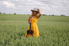 Women yellow dress and guitar pose in rye field Stock Images