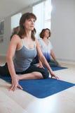 Women at yoga class practicing pigeon pose Stock Image