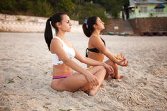 Women in Yoga meditation pose. At amazing sunset stock photos