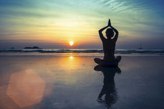 Women in Yoga meditation pose at amazing sunset. Royalty Free Stock Photos