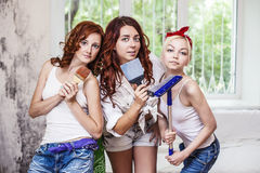 Women young beautiful girlfriends doing repairs in the house wit Royalty Free Stock Photo