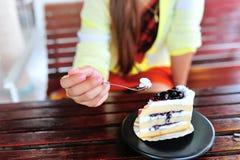 Womenl que come o bolo extravagante na luz suave Fotos de Stock