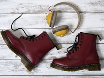 Womens accessories, footwear burgundy boots, yellow wireless headphones. Fashion outfit, shopping concept, flat lay royalty free stock image