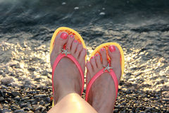Womens ankle at the edge of sea water Royalty Free Stock Photo
