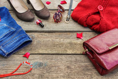 Womens autumn clothing and accessories: red sweater, pants, handbag, beads, sunglasses, nail polish, hair band, belt. On wooden background. Top view Stock Image