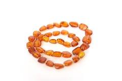 Womens bead necklace amber. Luxury background. Womens bead necklace made of amber  on white background. Photo Macro shot jewelry Royalty Free Stock Photo