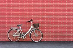Bike against a Red Brick Wall. Womens bicycle against a dark red brick wall stock images