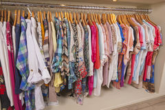 Womens clothes hanging on rail. Variety of colorful womens clothing hanging on rail in fashion shop royalty free stock photography