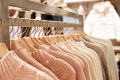 Womens clothes on wood hangers on rack. Pink womens clothes on wood hangers on rack in fashion store . closet women sweaters close up royalty free stock photos