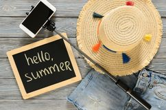 Womens clothing, accessories denim shorts, straw hat, cellphone. Selfie stick, chalkdoard on grey wooden background. Text Hello summer. Trendy fashion outfit Royalty Free Stock Photography