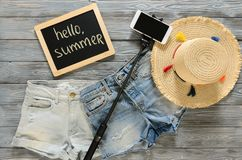 Womens clothing, accessories denim shorts, straw hat, cellphone. Selfie stick, chalkdoard on grey wooden background. Text Hello summer. Trendy fashion outfit Royalty Free Stock Photos